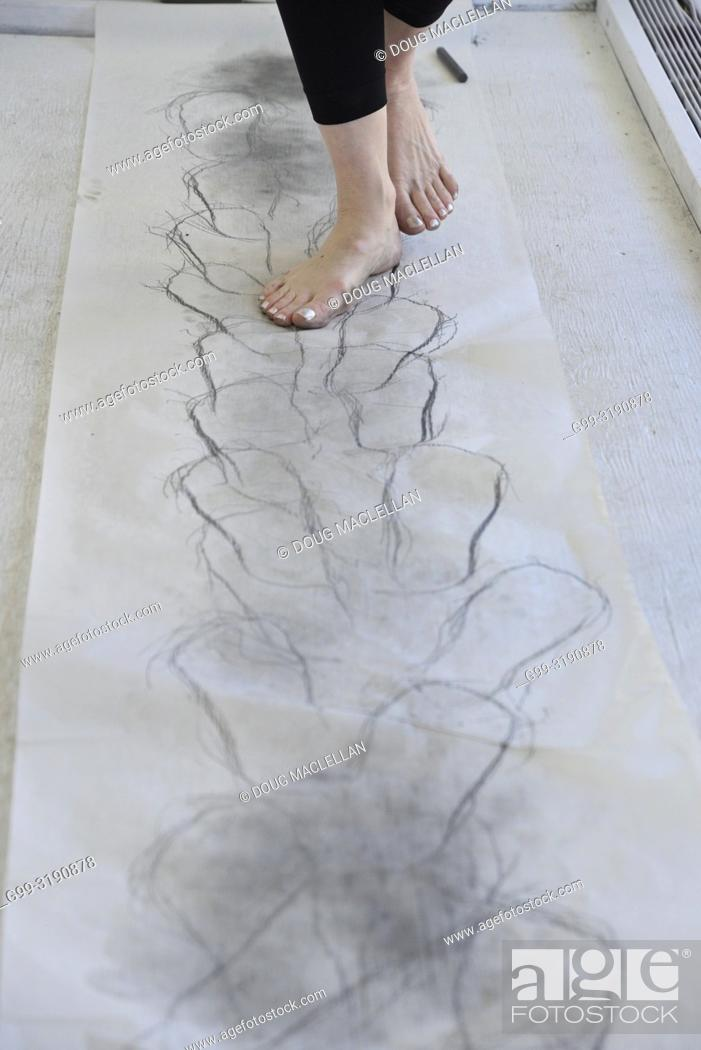 Stock Photo: A barefoot woman artist walks on smudged paper during a performance, Windsor, Canada.