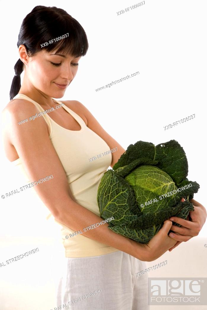 Stock Photo: woman carrying whole green cabbage.