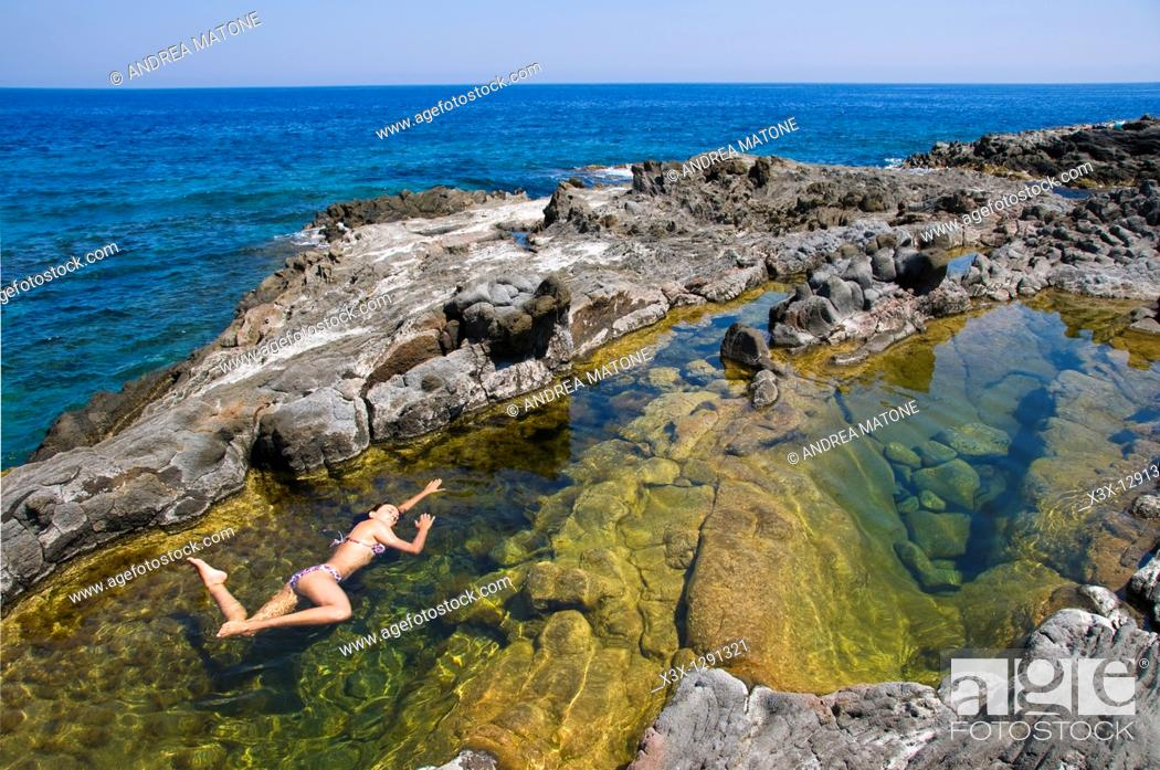 Stock Photo: Woman floating in colorful water pool by the sea  Pantelleria Island, Sicily, Italy.