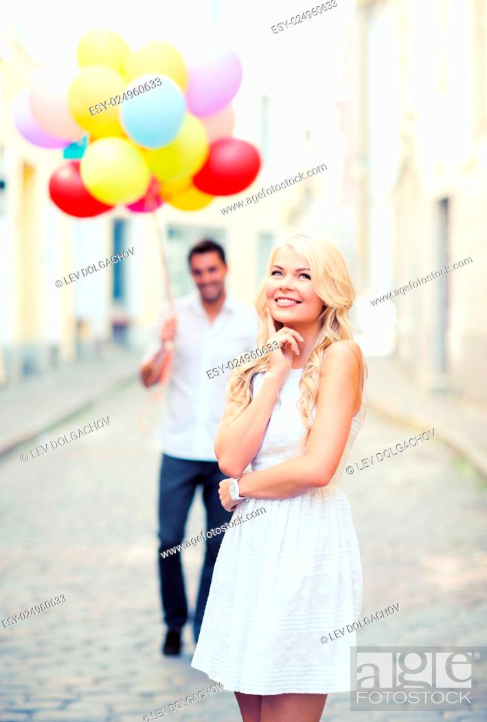Stock Photo: summer holidays, celebration and relationships concept - woman and man with colorful balloons in the city.