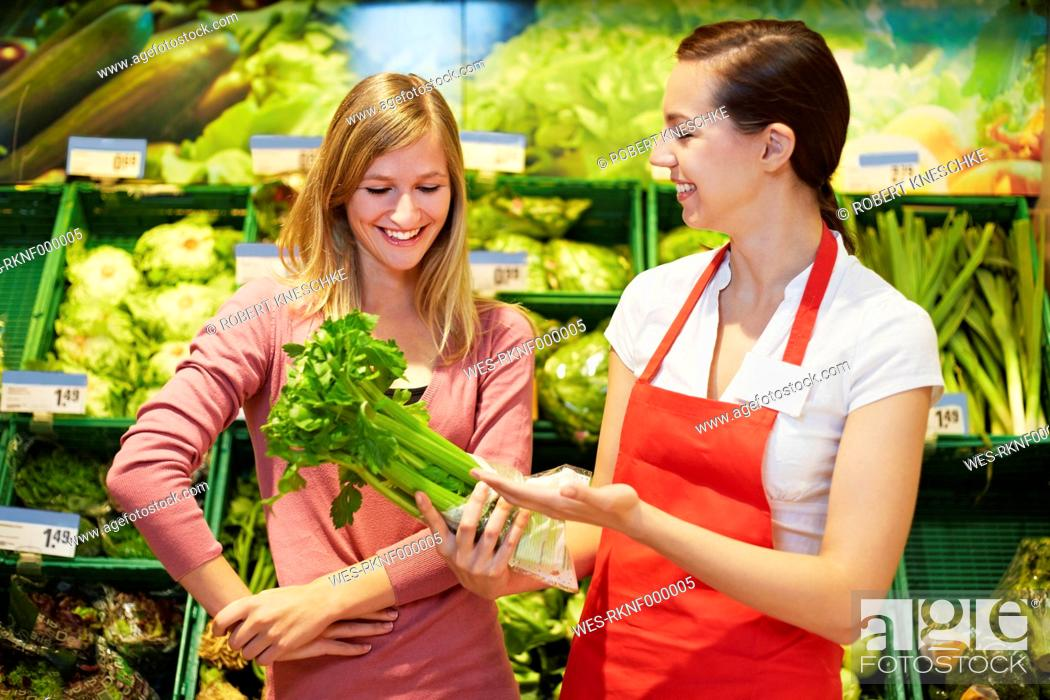 Stock Photo: Germany, Cologne, Young womens with celery in supermarket.