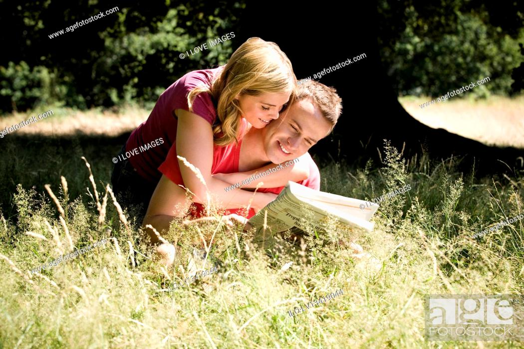 Stock Photo: A young couple sitting on the grass, reading a newspaper.