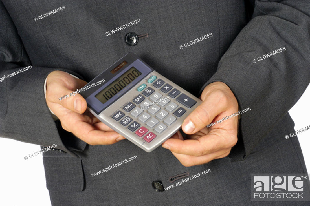 Stock Photo: Mid section view of a businessman holding a calculator.