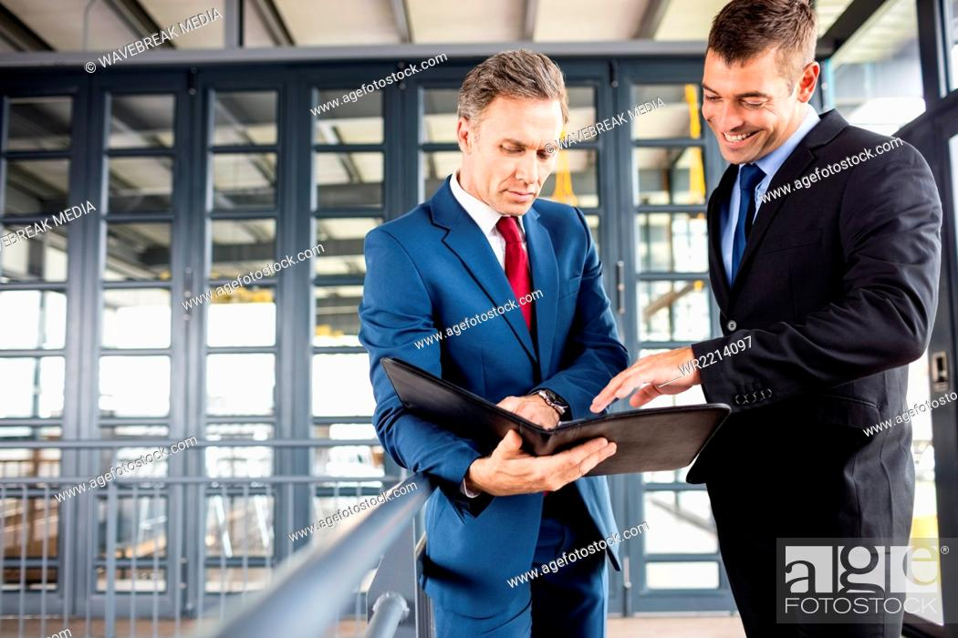 Stock Photo: Businessmen talking together while looking folder.