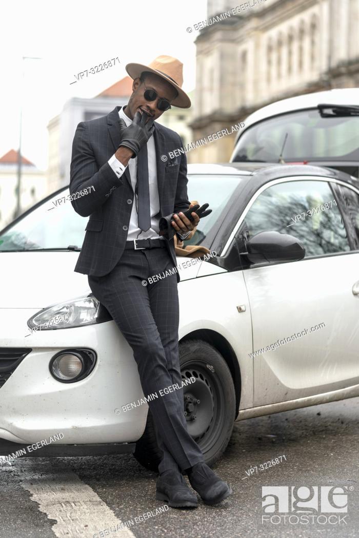 Stock Photo: Man leaning on car, Munich, Germany.