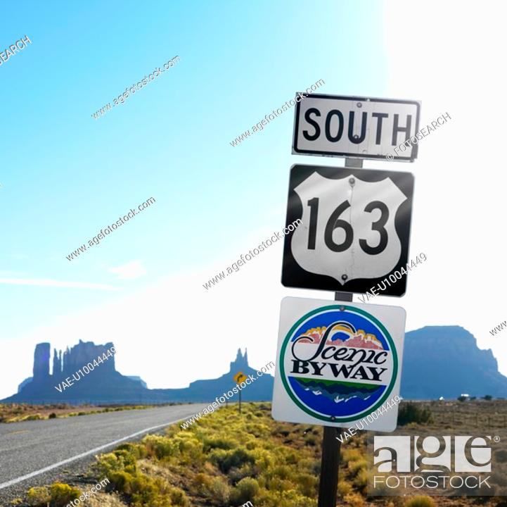 Stock Photo: Sign for Scenic Byway 163 south beside road with rock formations in background in Monument Valley, Utah.