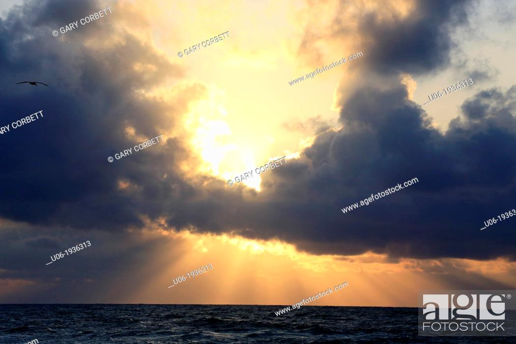 Stock Photo: Storm clouds and sun bursts over a rough sea in the Caribbean.