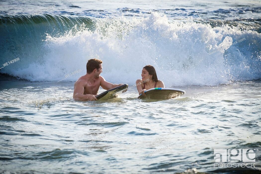 Stock Photo: Young woman and man waiting for wave to ride out on boogie board.