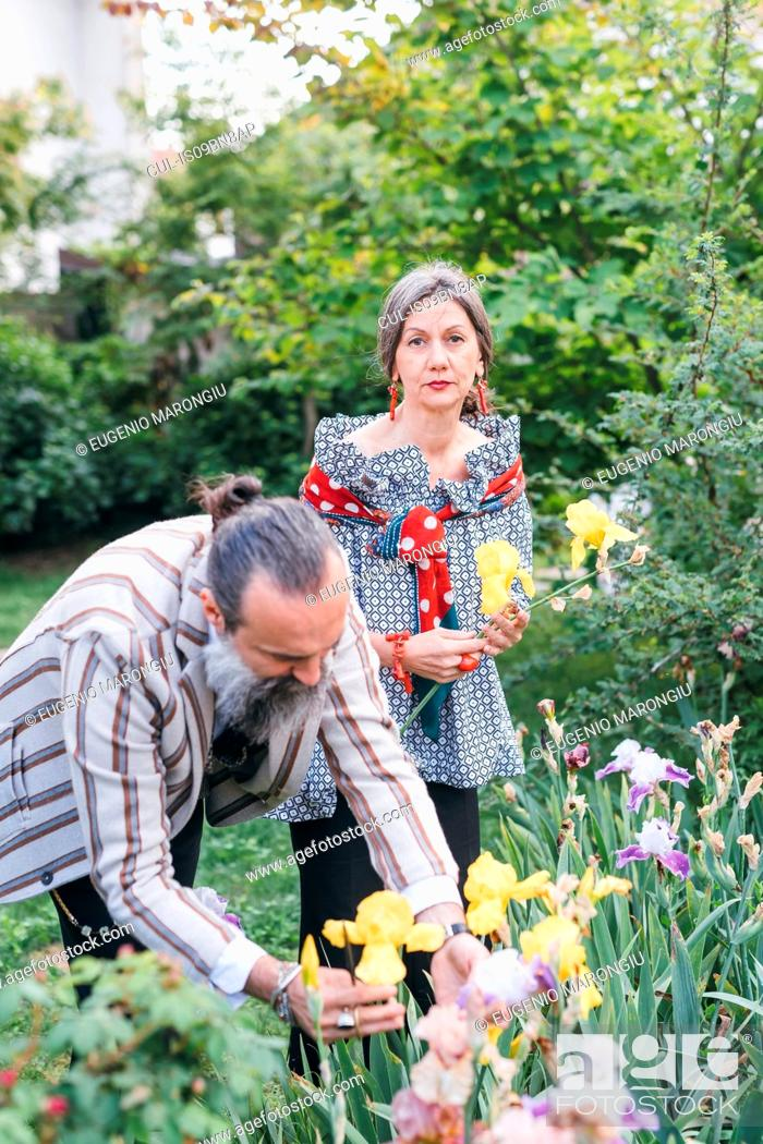 Stock Photo: Couple picking flowers from garden.