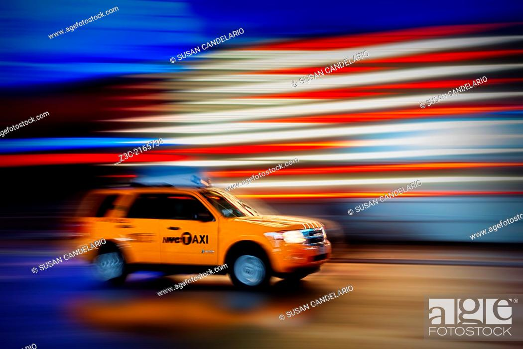 Stock Photo: New York City Taxi whizzes along Times Square during the rain.