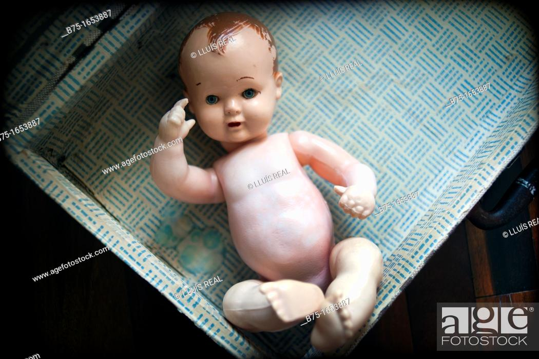 Stock Photo: doll-baby naked in a suitcase.