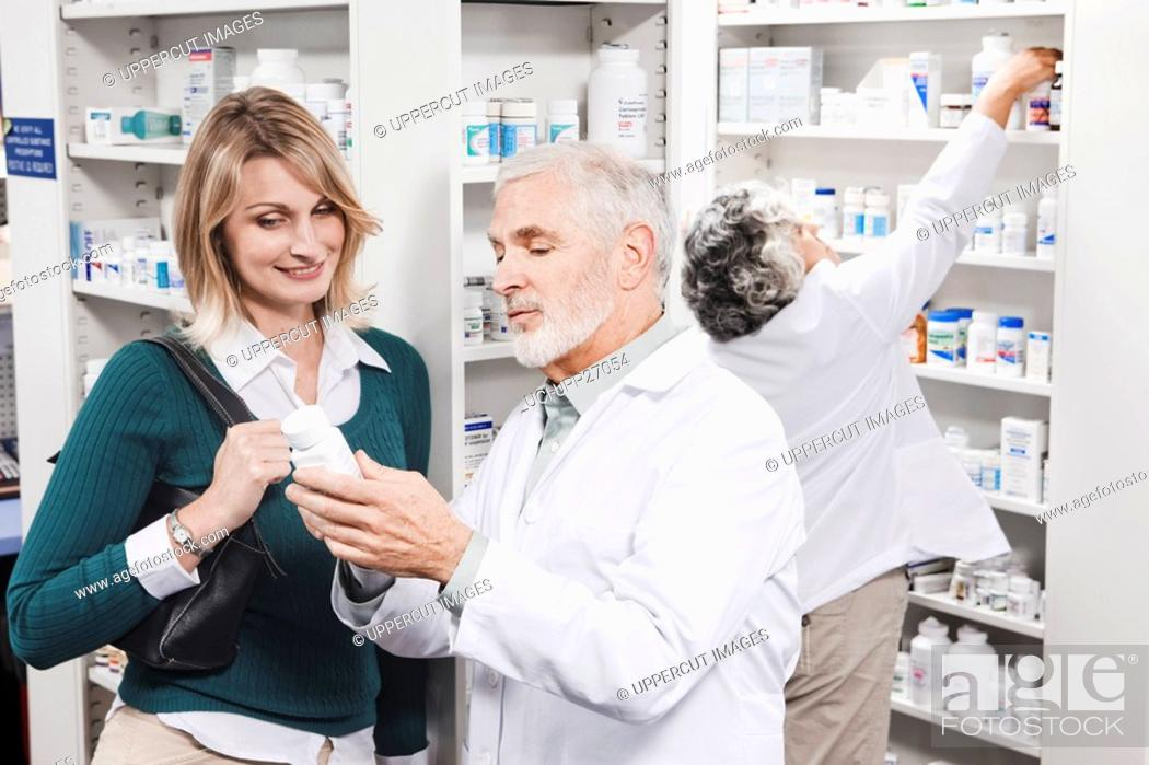 Stock Photo: Pharmacist explaining medication to customer.