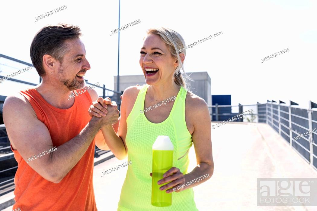 Photo de stock: Fit couple jogging in the city, having fun, taking a break.