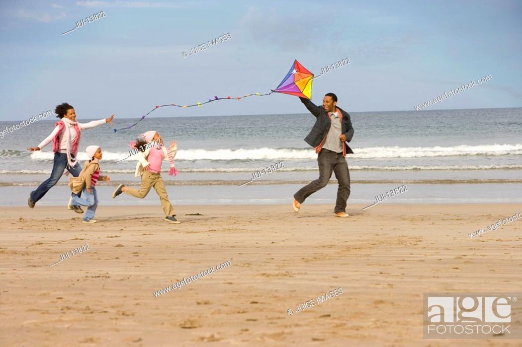 Stock Photo: Family of four with kite on beach.