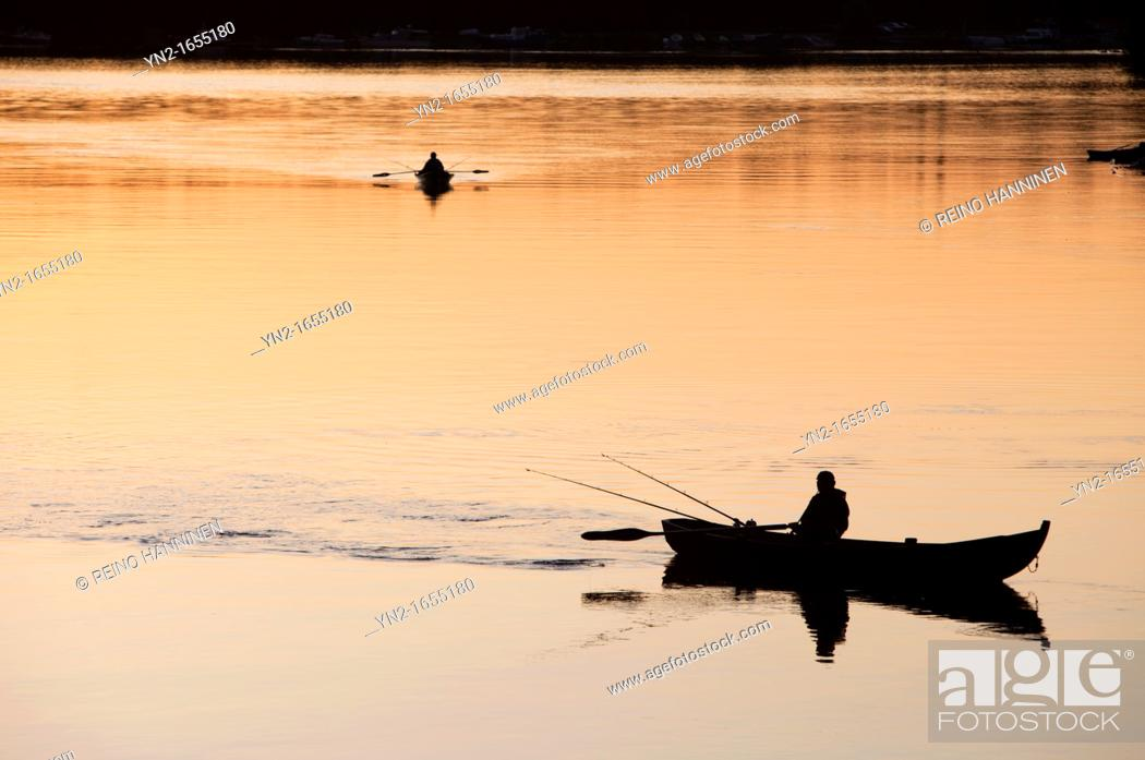 Stock Photo: Fisherman trolling from a rowboat at sunset at river Oulujoki. Location Finland Tuira Oulujoki Oulu Finland Scandinavia Europe.