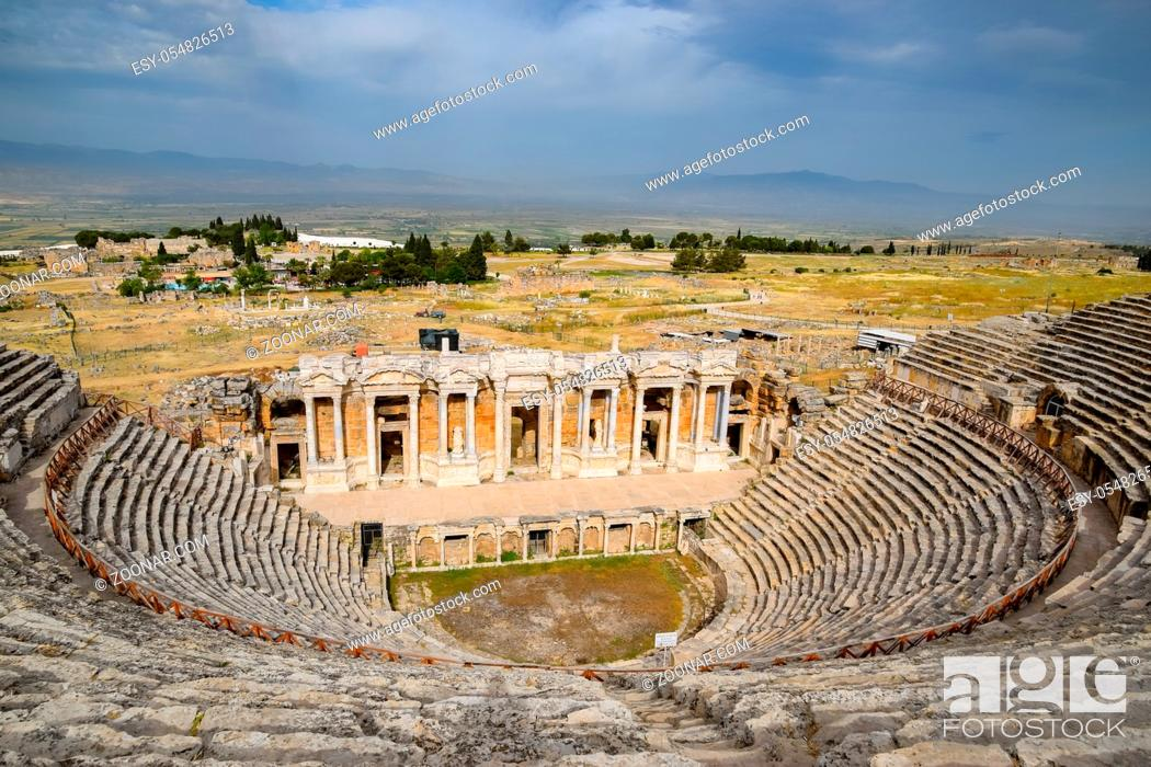 Stock Photo: Ancient antique amphitheater in the city of Hierapolis in Turkey. Steps and antique statues with columns in the amphitheater.
