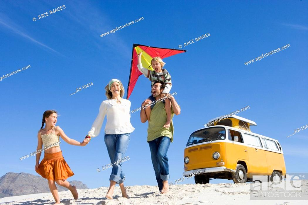 Stock Photo: Family of four on beach, daughter 5-7 holding mother's hand, son 6-8 on father's shoulders with kite, low angle view.
