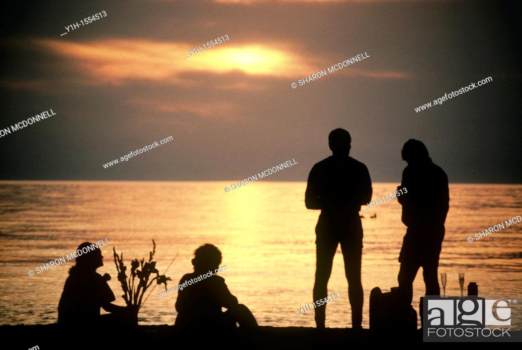 Stock Photo: Two couples picnic on the beach watching the sun set and sharing food.
