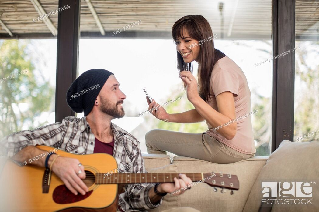 Imagen: Young man at home sitting on couch playing guitar for woman.