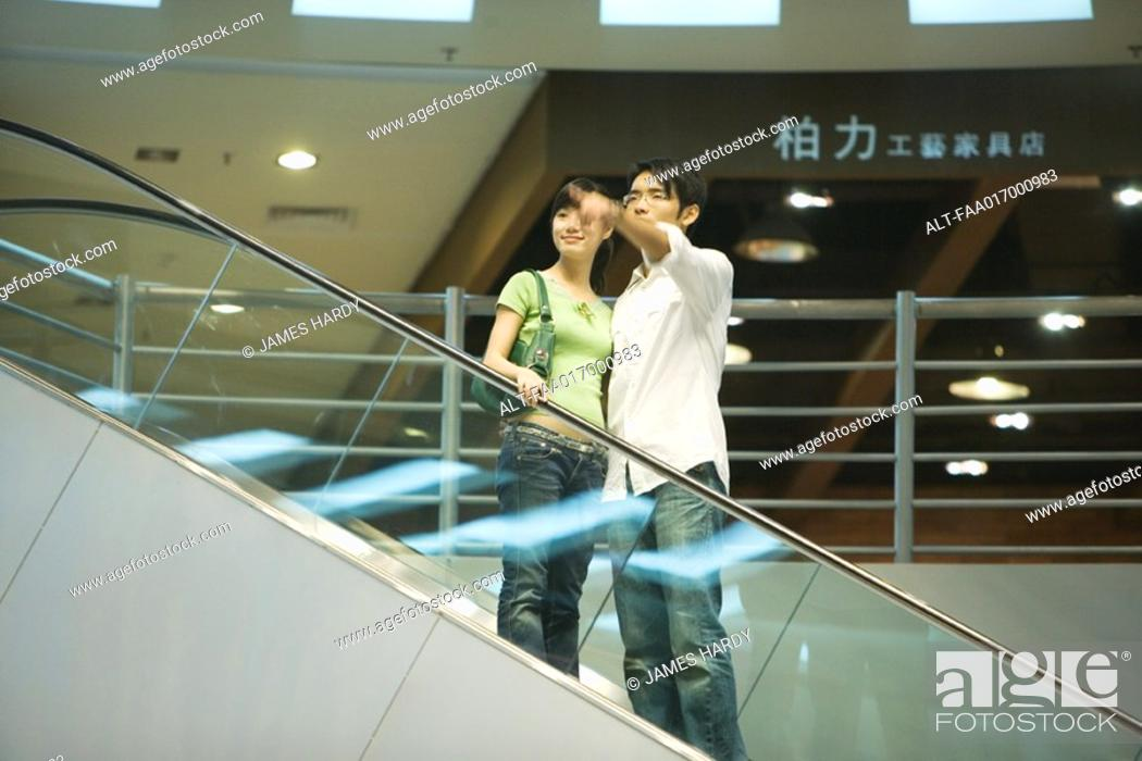 Stock Photo: Couple taking escalator in shopping mall, man pointing out of frame.