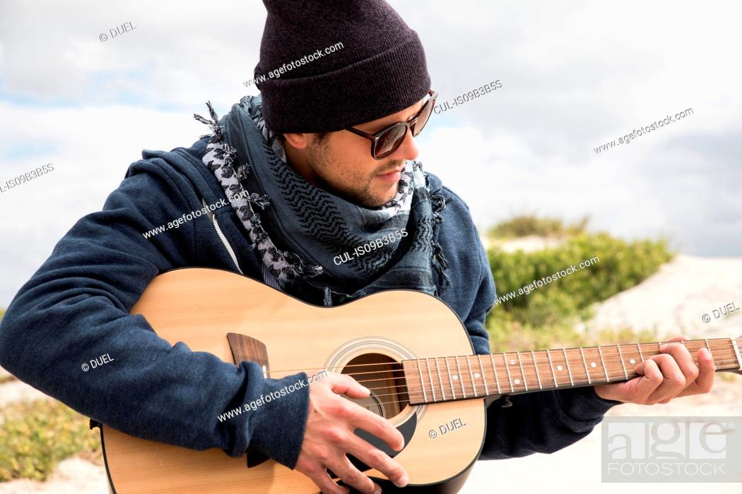 Stock Photo: Young man playing acoustic guitar on beach, Western Cape, South Africa.