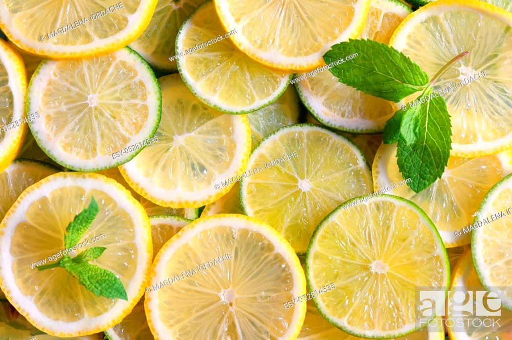 Stock Photo: Fresh green and yellow lemon slices background.