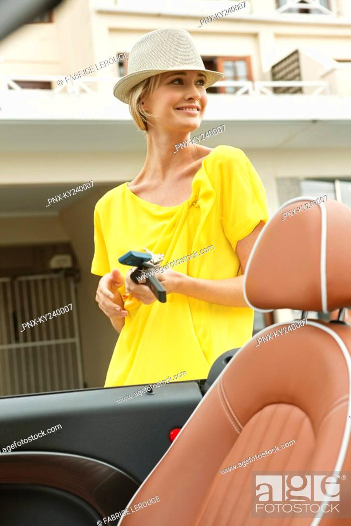 Stock Photo: Woman standing near a car and smiling.