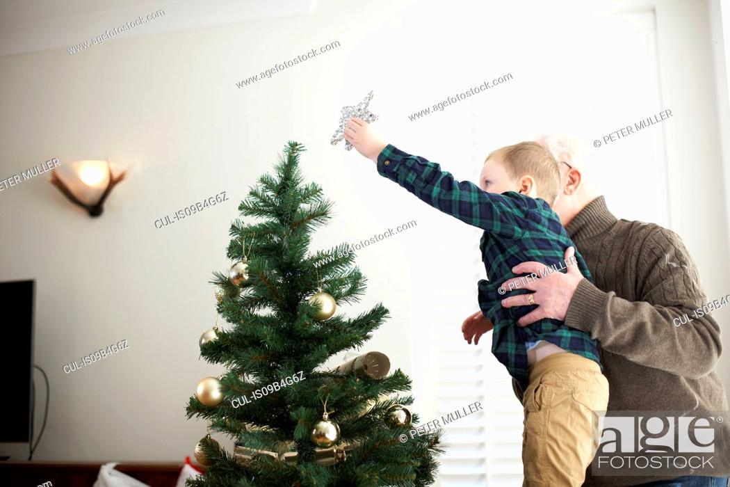 Stock Photo: Senior man lifting grandson to place star on christmas tree.