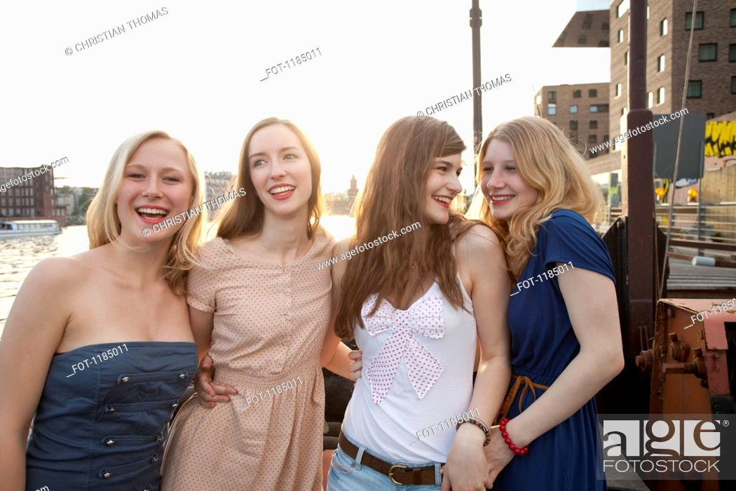 Stock Photo: Four female friends standing side by side, Spree River, Berlin, Germany.