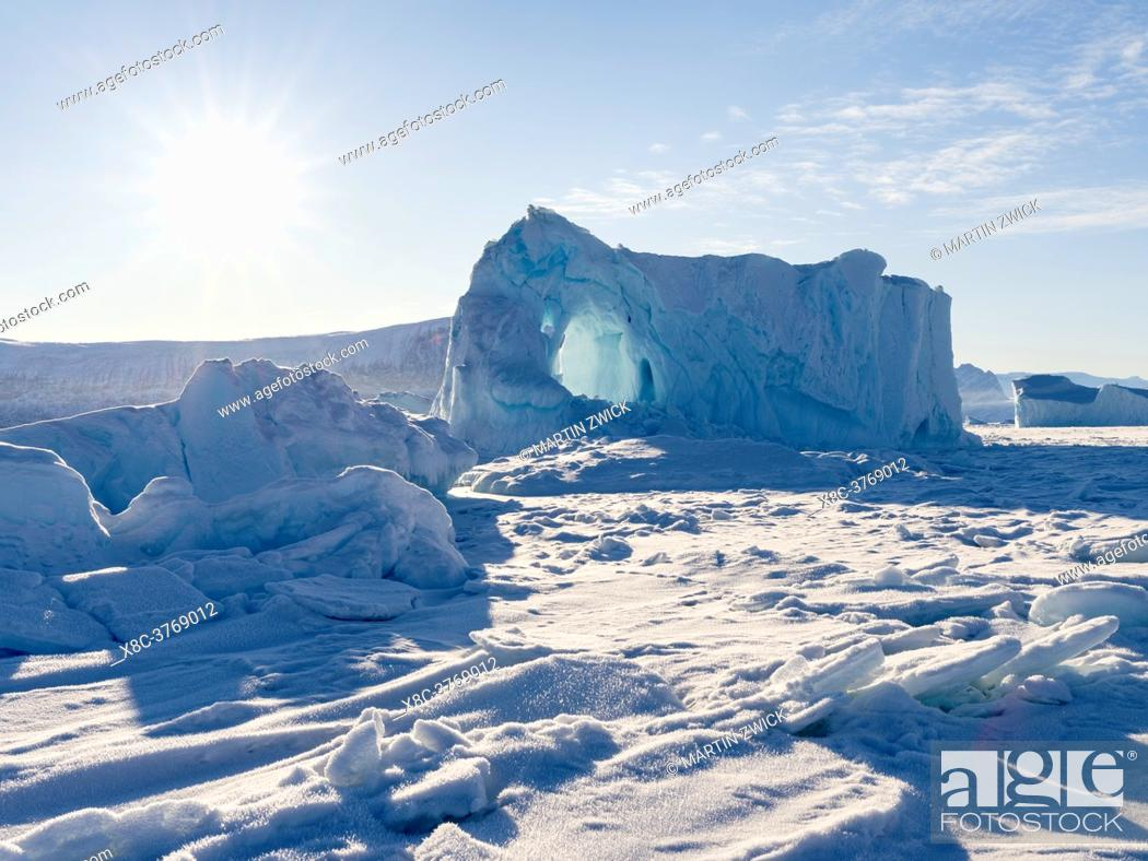 Stock Photo: Icebergs frozen into the sea ice of the Uummannaq fjord system during winter in the the north west of Greenland, far beyond the polar circle.