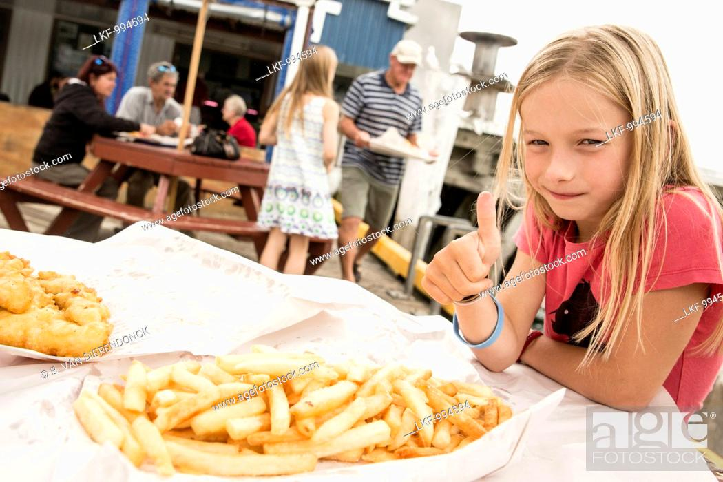 Stock Photo: A girl with fish and chips at Tauranga, North Island, New Zealand.