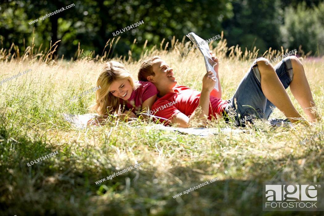 Stock Photo: A young couple lying in the grass, reading newspapers.