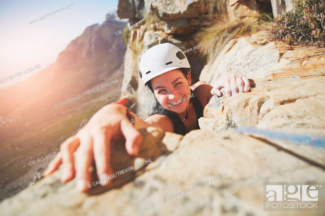 Stock Photo: Portrait smiling, confident rock climber reaching for rock.