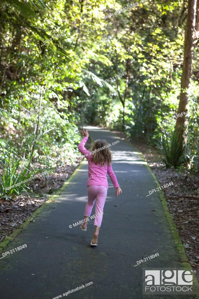 A young girl wearing pink walks down a trail in springbrook
