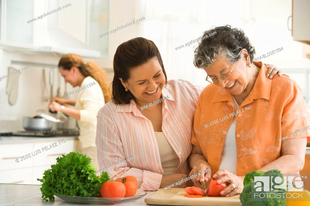 Stock Photo: Hispanic woman and adult daughter chopping vegetables.