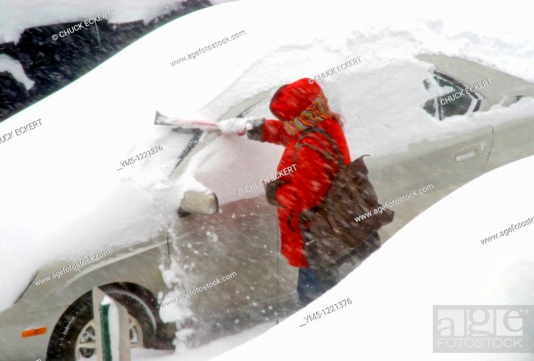 Stock Photo: Woman clearing heavy snowfall from car during storm.
