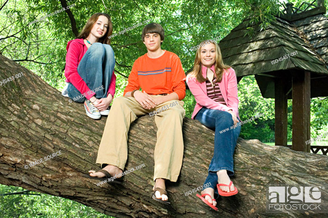Stock Photo: Three teenagers sitting on a branch.