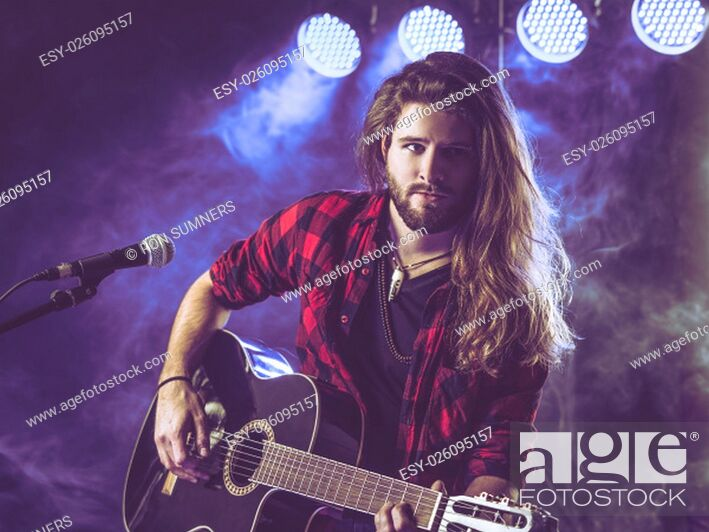 Stock Photo: Photo of a young man with long hair and a beard playing an acoustic guitar on stage with lights and concert atmosphere..