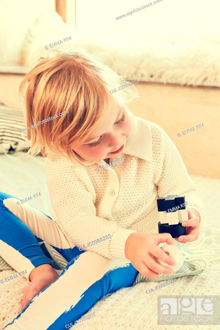 Stock Photo: Female toddler sitting on bed stacking building bricks.