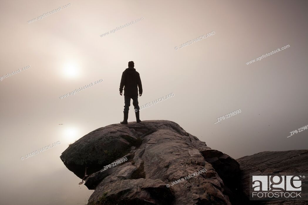 Stock Photo: A man stands at the edge of a rocky outcrop looking into the fog as the sun rises. Algonquin Provincial Park, Ontario, Canada.