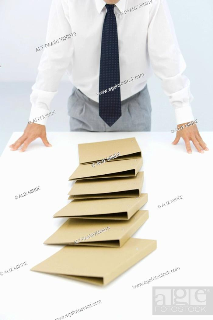 Stock Photo: Binders lying on table after a chain reaction of being pushed over, cropped view of businessman.