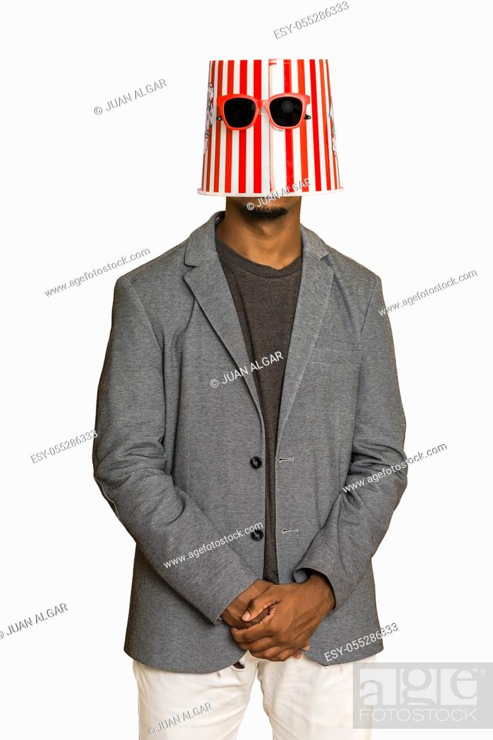 Stock Photo: Modern black guy in smart casual clothes wearing popcorn bucket and sunglasses on head against gray background.