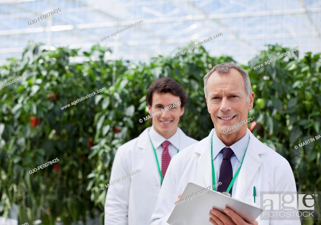 Stock Photo: Scientist using clipboard in greenhouse.