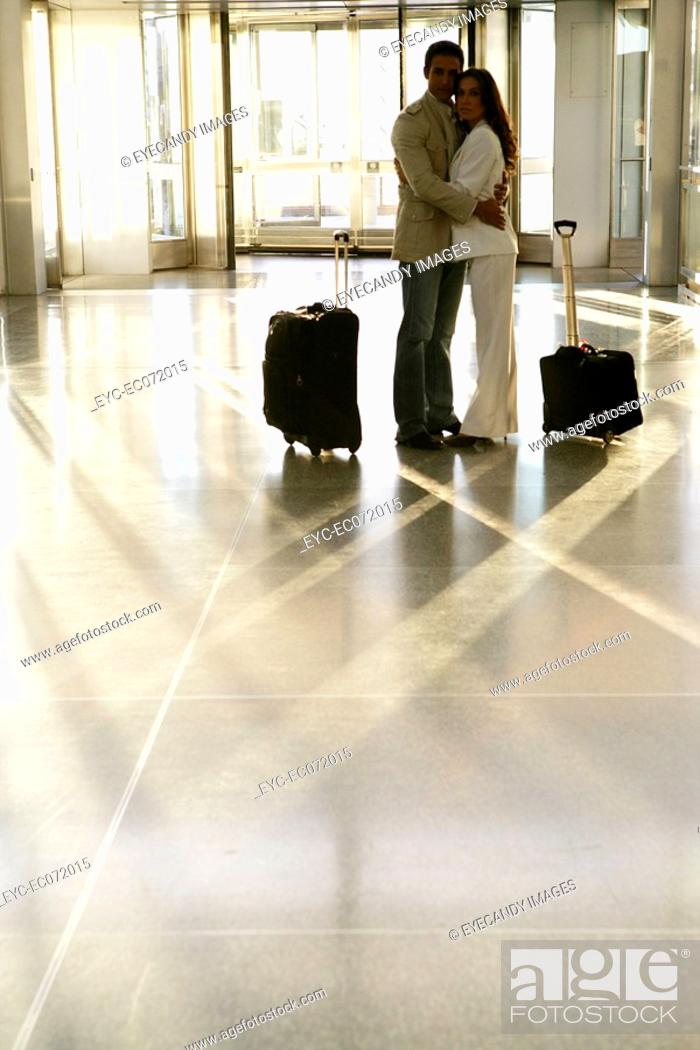Stock Photo: Young couple standing in airport with luggage.