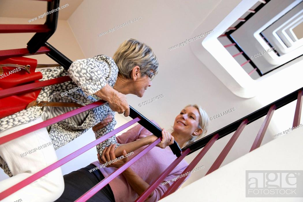 Photo de stock: Elderly woman being helped by another woman to climb the stairs.