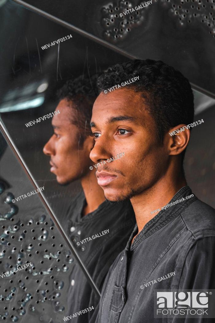 Stock Photo: Portait of young man at mirrored wall.