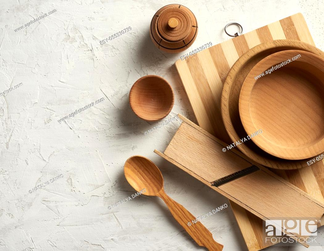 Stock Photo: empty wooden round plates and new cutting board on gray background, top view, copy space.