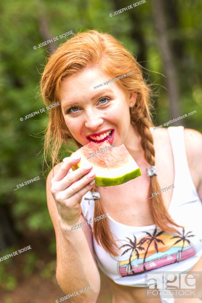 Photo de stock: A happy 27 year old redhead woman eating a watermelon outdoors.
