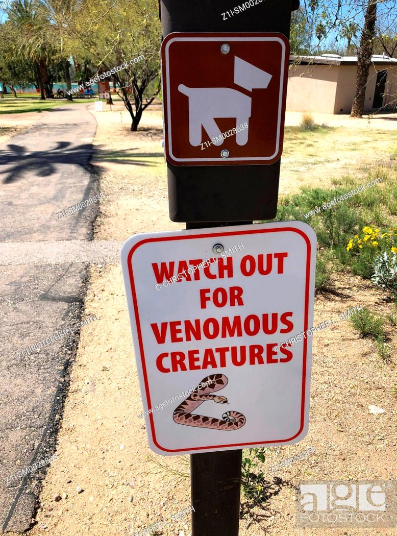 """Stock Photo: """"""""""""""""""""Watch out for Venomous Creatures"""""""" sign in a park in Arizona."""