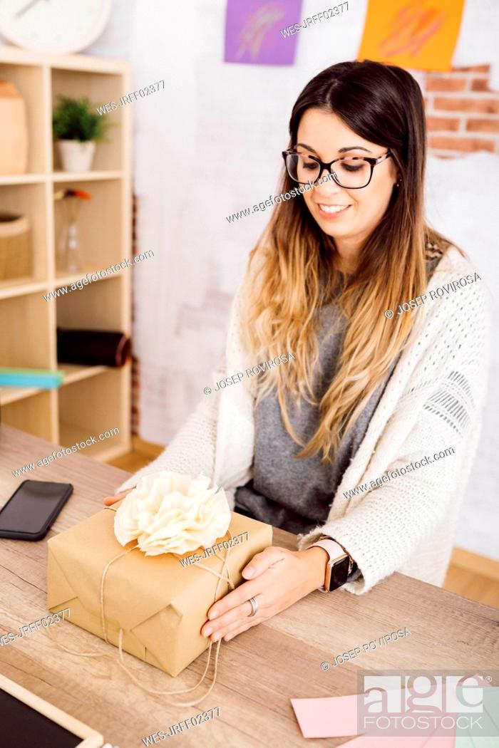 Stock Photo: Young woman showing a wrapped gift in her studio.